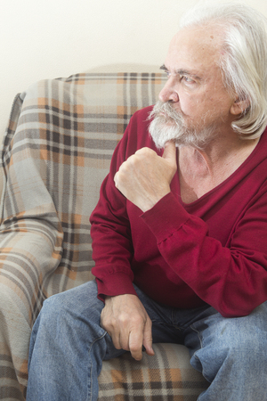 A handsome sick old man with a beard and a mustache with long white hair in a nursing home sits in an armchair all alone and reflects on the past years
