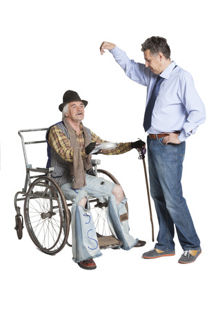 A successful manager, laughing and mocking, gives a beggar sitting in a wheelchair a dollar bill Stock Photo