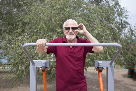 Attractive senior man trains on sporting equipment in a city in the open air. The concept of a healthy lifestyle and accessibility of sports training for every person. Available sports equipment in a public place. Archivio Fotografico - 122681932