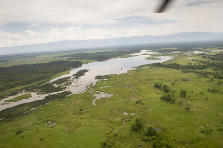 The rivers and lakes of Eastern Siberia from the altitude. A view from the cockpit of the helicopter to the lakes and the river in the Siberian taiga. View from the cockpit of a flying helicopter over the Siberian taiga lakes and rivers. Stock Photo