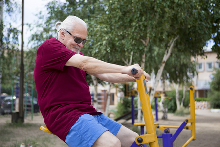 Attractive senior man trains on sporting equipment in a city in the open air. The concept of a healthy lifestyle and accessibility of sports training for every person. Available sports equipment in a public place.