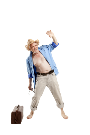 Elderly man posing in the studio on a white background depicting a vacationer arriving at the beach Stock Photo