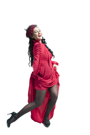 Young woman stinging brunette in a long red dress dancing and posing in the studio
