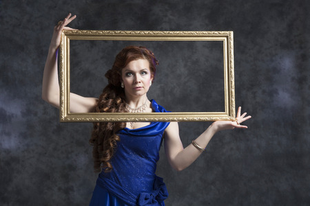 Young woman in blue classic evening dress posing in the studio on a gray background with a frame for a picture Banco de Imagens