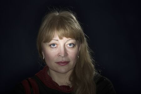 Portrait of a beautiful fifty-year-old blonde on a dark background with classic facial features and blue eyes underlined with light