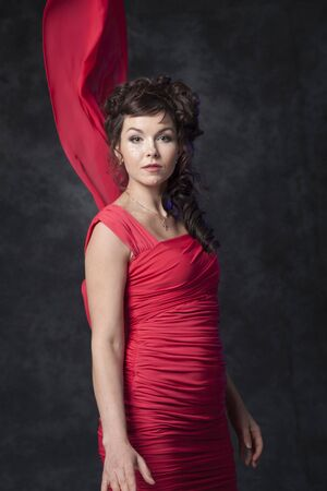 A charming brunette in a stylish fashionable red dress makes a defile in the studio on a black background. 写真素材 - 134676167