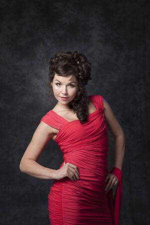 A charming brunette in a stylish fashionable red dress makes a defile in the studio on a black background.