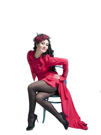 Young woman stinging brunette in a long red dress dancing and posing in the studio 写真素材 - 134676174