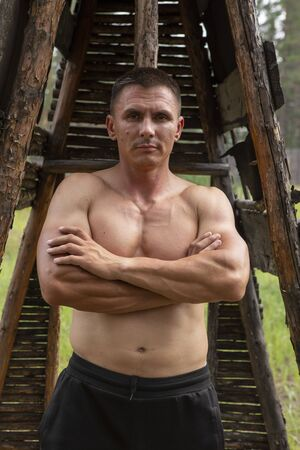 Attractive muscular man in a wooded area, against the background of a house of old thin poles demonstrates a muscular body 写真素材 - 134676179