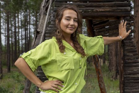 Beautiful Russian girl posing on the background of a house of old thin poles at the cottage in the village 写真素材