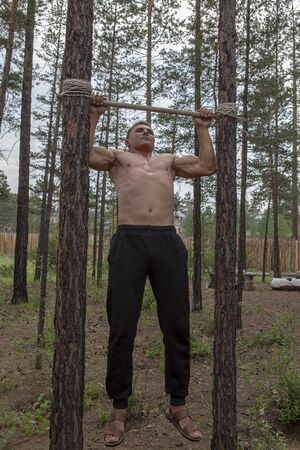 The athlete does push-ups on a makeshift bar between trees in a summer cottage