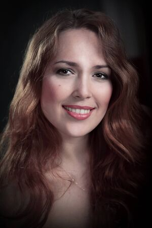 Very beautiful young brown-haired woman mysteriously smiles in the studio on a black front