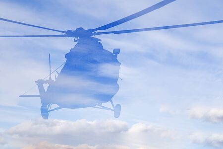 Helicopter flies through clouds in a blue sky in contour natural light
