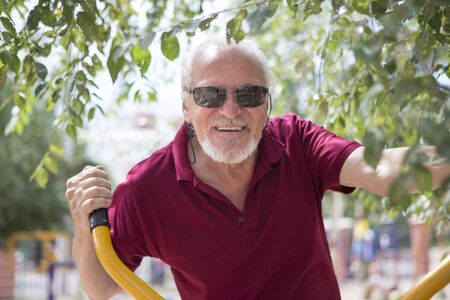 Attractive senior man trains on sporting equipment in a city in the open air. The concept of a healthy lifestyle and accessibility of sports training for every person. Available sports equipment in a