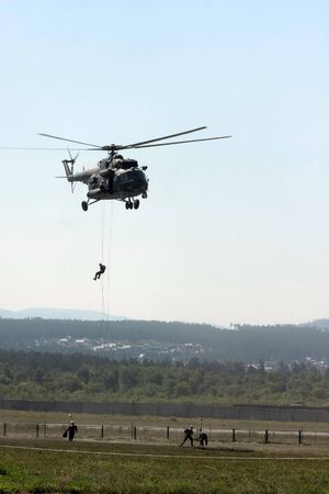 Training of firefighters at the airport with a simulation of a plane crash and a helicopter fire. Landing firefighters from a military helicopter using fast rope technique