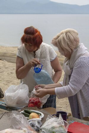 Girlfriends prepare the ingredients for the preparation of barbecue on the shore of Lake Baikal