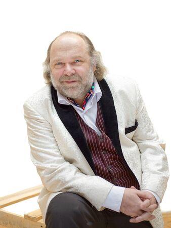 Charmanter fröhlicher Mann mittleren Alters mit Bart und Schnurrbart in einem weißen Smoking, der für ein Porträt auf einem weißen Hintergrund aufwirft Standard-Bild