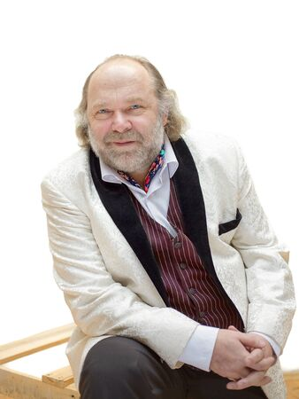 Charming cheerful middle-aged man with a beard and mustache in a white tuxedo posing for a portrait on a white background Imagens