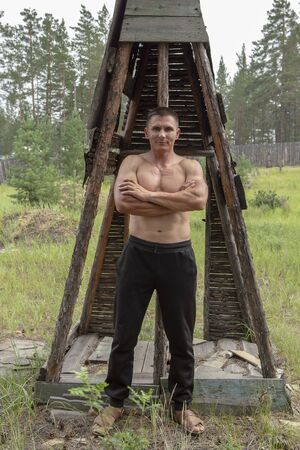 Attractive muscular man in a wooded area, against the background of a house of old thin poles demonstrates a muscular body