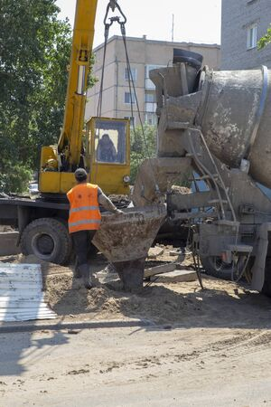 Reception of concrete mortar from the mixer in the tank for pouring into the wooden formwork of the trench