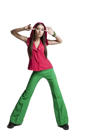 Beautiful girl in a red blouse and green pants posing in the studio