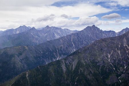 View of the mountains of the Tunkinsky National Park in the Republic of Buryatia of the Russian Federation from the cockpit of the helicopter. The name of the mountain range -  Eastern Sayans. 写真素材