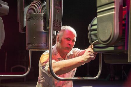 An electric operator repairs a spotlight on the stage of the theater