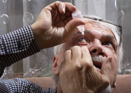 Self-instillation of eye drops in patients with glaucoma eyes. An elderly man with glaucoma. 写真素材 - 134419092