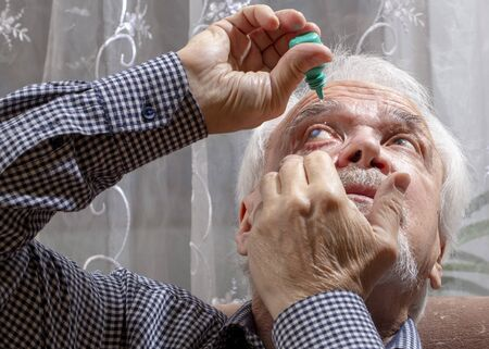 Self-instillation of eye drops in patients with glaucoma eyes. An elderly man with glaucoma. 写真素材 - 134419094