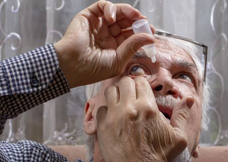 Self-instillation of eye drops in patients with glaucoma eyes. An elderly man with glaucoma. 写真素材 - 134419103