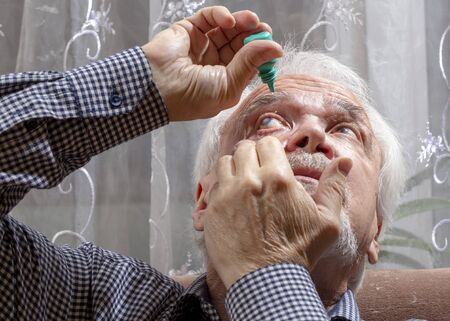 Self-instillation of eye drops in patients with glaucoma eyes. An elderly man with glaucoma. Imagens