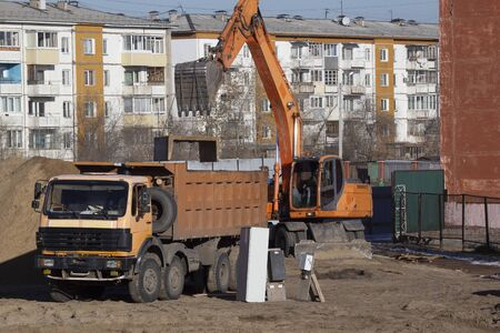 Loading a reinforced concrete block into a dump truck using an excavator bucket