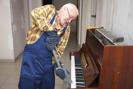 elderly man demount an old piano
