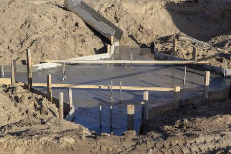 Pouring liquid concrete into the formwork for the foundation of a building under construction