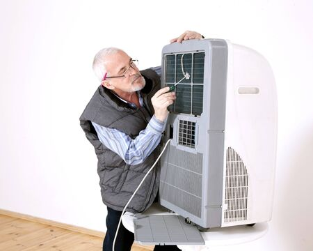gray-haired man in glasses repairing air conditioning