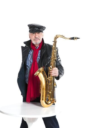 man in a jacket and hat with trumpet near the table on a white background