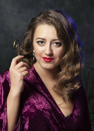 Sexy girl draped in purple velvet posing in studio 写真素材