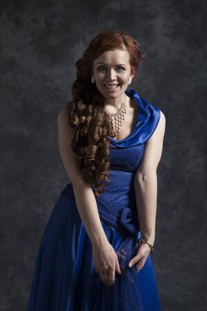 Young woman in a dark blue classic evening dress posing in the studio on a gray background. 写真素材