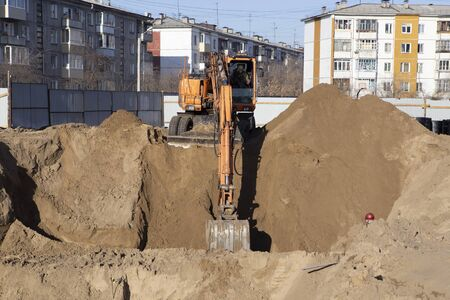 The excavator digs a foundation pit for pouring the foundation for the construction of the building 写真素材