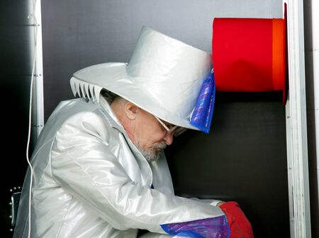 Magician in a white suit with hat sitting in a box before the show