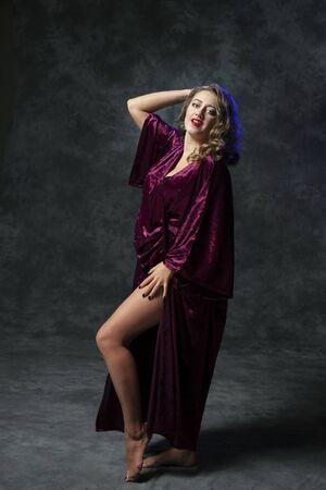 Sexy girl draped in purple velvet posing in studio