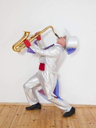 magician in a white suit and hat plays the trumpet
