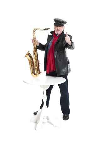 man in a jacket and hat with trumpet near the table showing trumb on a white background 写真素材