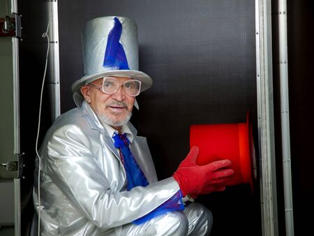 Magician in a white suit with hat sitting in a box before the show 写真素材