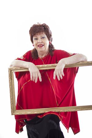 Thick woman of 60s in red long blouse posing in studio on white background