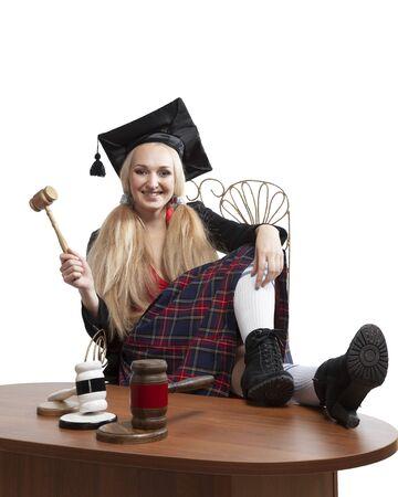 Girl law student in traditional graduation costume hooligan judges hammer Standard-Bild