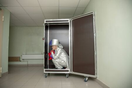 Sad clown squatting in a box for transportation of props and suffers