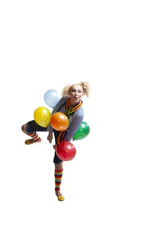 Clown girl with balloons dancing, jumping, grimacing and grimacing in studio carved on a white background