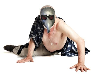 Sick elderly man half-naked in a plague mask lies on the floor