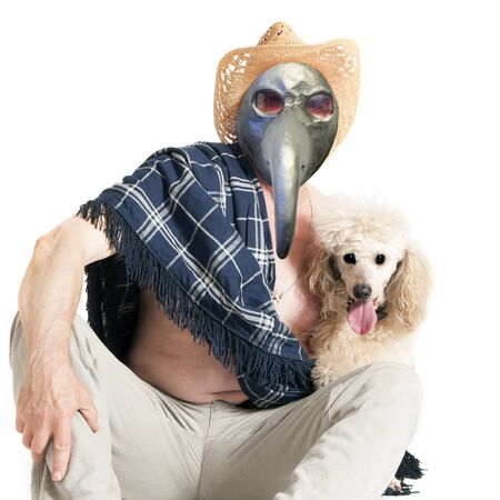 A sick elderly man in a plague mask and sombrero is sitting on the floor, hugging a poodle. 写真素材